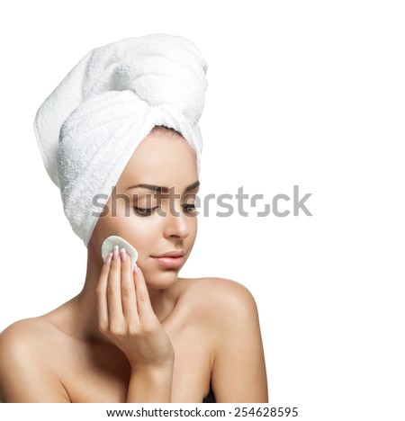Young woman with a towel on her head, healthy pure skin and removes makeup from the face with cotton pad on white background - stock photo