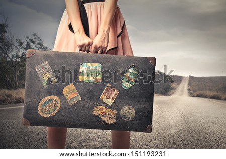 young woman with a vintage suitcase in the middle of a deserted road - stock photo