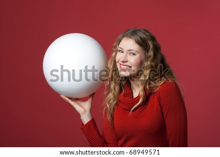 young woman with a white ball as a blank display - stock photo