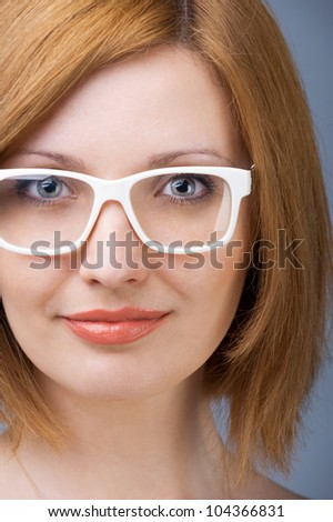 Young woman with a white plastic glasses keeping an eye contact. - stock photo