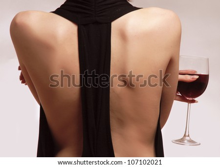 Young woman with a wineglass over the wall, isolated on grey - stock photo