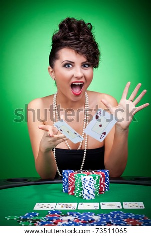 Young woman with aces four of a kind playing poker and throwing the cards in the excitement
