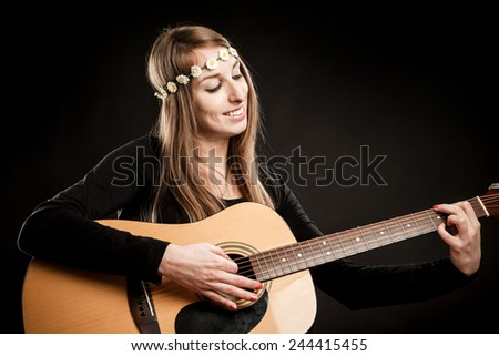 Young woman with acoustic guitar and flower hairband - stock photo