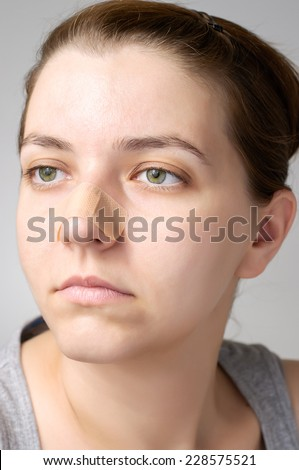 Young woman with adhesive bandage on her nose - stock photo