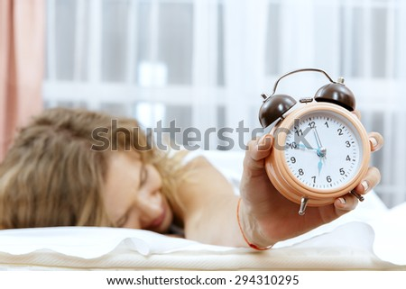 Young woman with alarmclock on the bed.