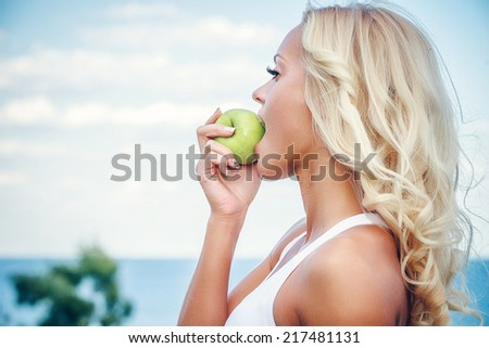 Young woman with an apple against sky background - stock photo