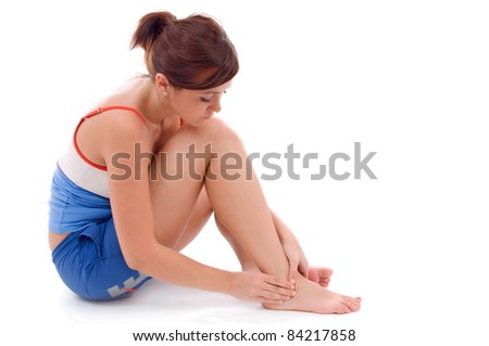 Young woman with an expression of severe pain in his leg. White background. - stock photo