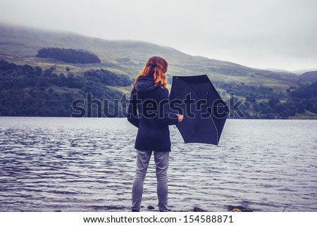 Young woman with an umbrella standing in lake - stock photo