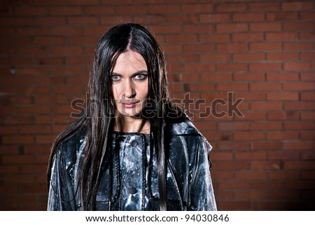Young woman with angry look after she got wet in the rain - stock photo