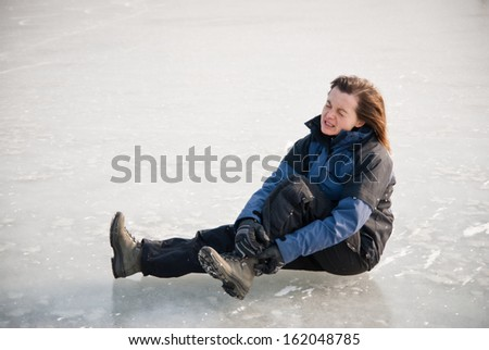 Young woman with ankle injury on frozen icy lake - stock photo