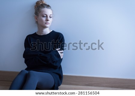 Young woman with anxiety disorder sitting on the floor