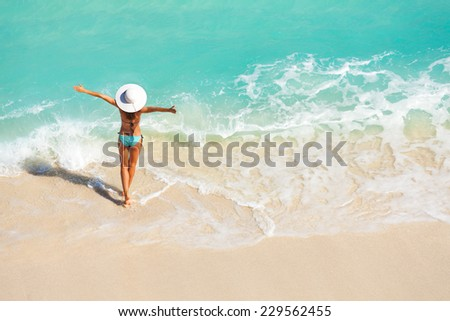 Young woman with arms apart on sand beach - stock photo
