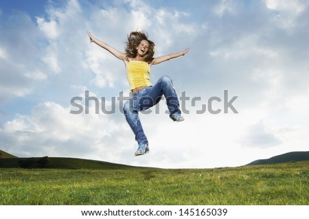 Young woman with arms outstretched screaming while jumping in park - stock photo