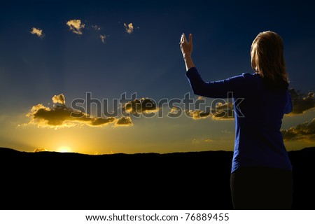 Young woman with arms raised in praise worshiping at sunrise - stock photo