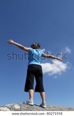 young woman with arms wide open against blue sky