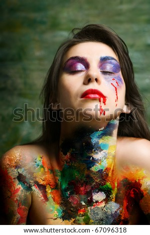 Young woman with art oil paints over naked body and disorderly stack in layers of make up on face - stock photo
