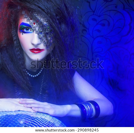 Young woman with artisric visage posing with disco-ball and smoke - stock photo