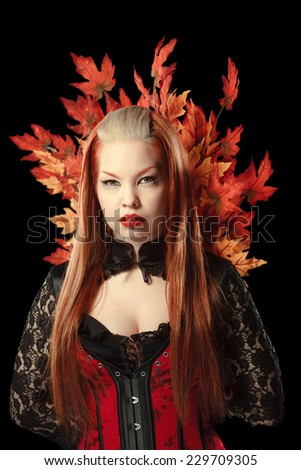 Young woman with autumn maple leaves isolated on black background - stock photo