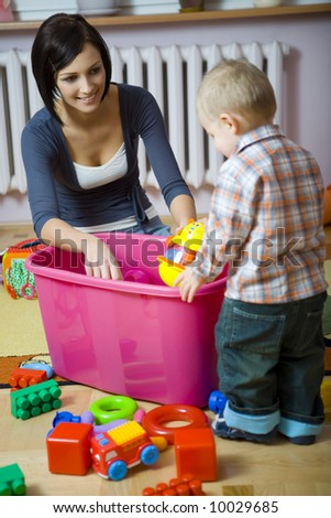 Young woman with baby boy during plaing. Woman showing toy to baby. They are at container with toys. Baby standing back to camera. Front view. - stock photo
