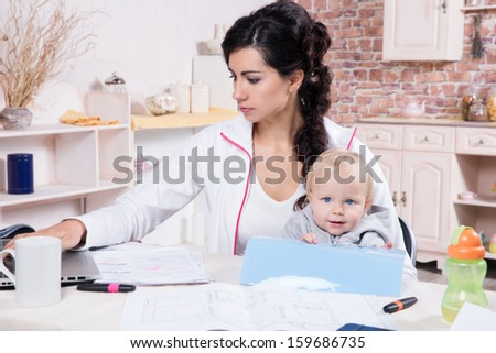 Young Woman With Baby Working From Home - stock photo