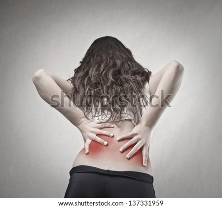 young woman with back pain - stock photo
