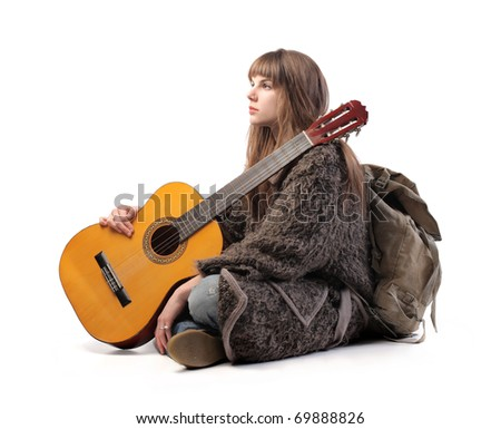 Young woman with backpack and guitar - stock photo