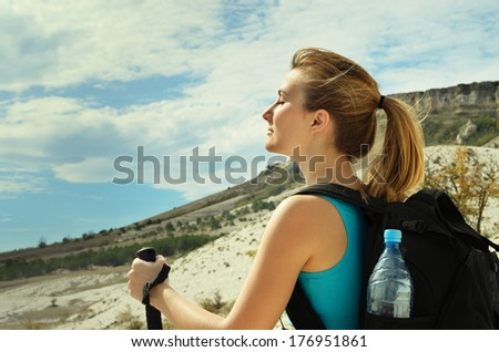 Young woman with backpack and trekking poles in mountains. - stock photo