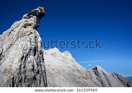 Young woman with backpack climbing along sharp alpine ridge