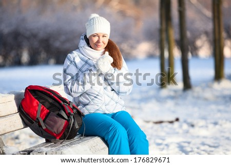 Young woman with backpack heating hands in mittens at winter, copyspace - stock photo