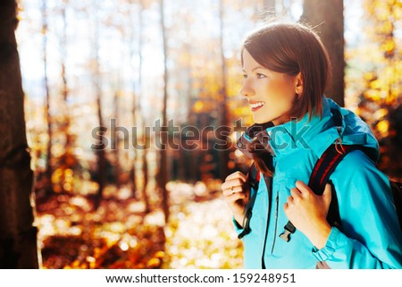 young woman with backpack hiking during autumn - stock photo