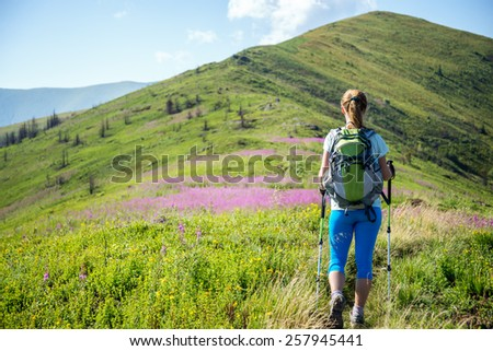 Young woman with backpack hiking in the mountains - stock photo
