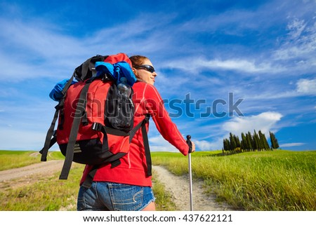 Young woman with backpack hiking in the mountains on field - stock photo