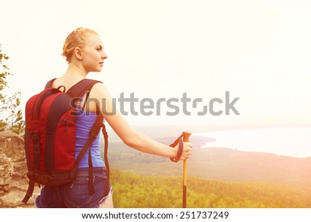 young woman with backpack hiking in the mountains. people outdoors - stock photo