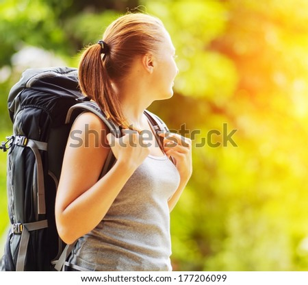 Young woman with backpack in a woods. Hiking at summertime.