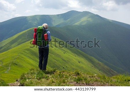 Young woman with backpack looking for adventure in mountains
