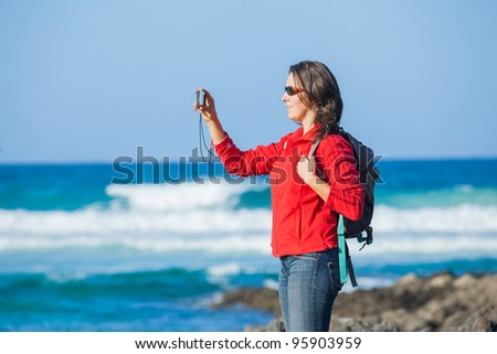 Young woman with backpack photographing a beautiful marine view - stock photo