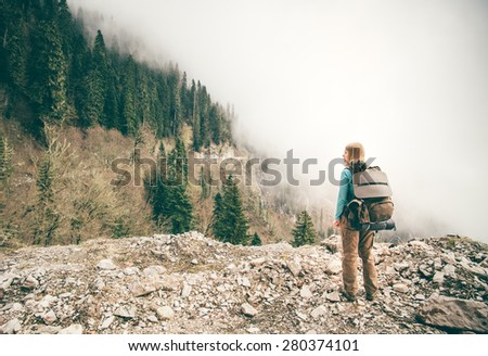 Young Woman with backpack relaxing outdoor with foggy forest on background Lifestyle Travel concept Summer vacations - stock photo