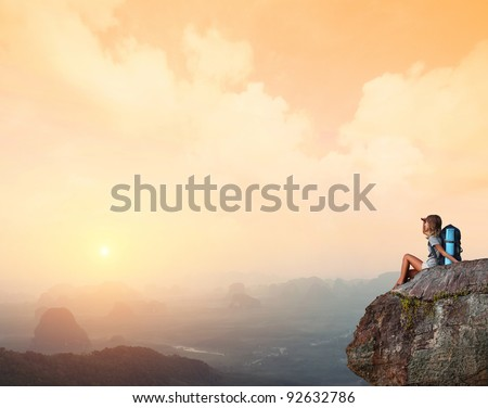 Young woman with backpack sitting on a cliff and enjoying a sunset