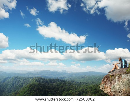 Young woman with backpack sitting on cliff and looking to a sky