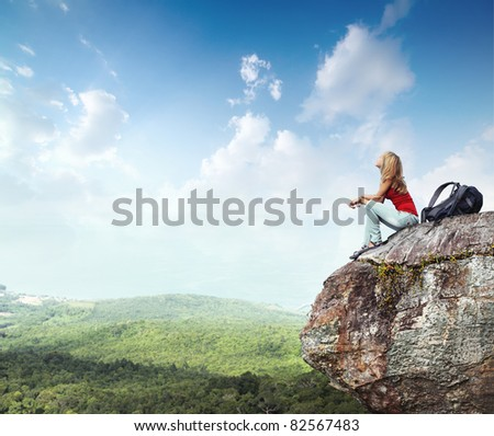 Young woman with backpack sitting on cliff's edge and looking to a sky with clouds - stock photo