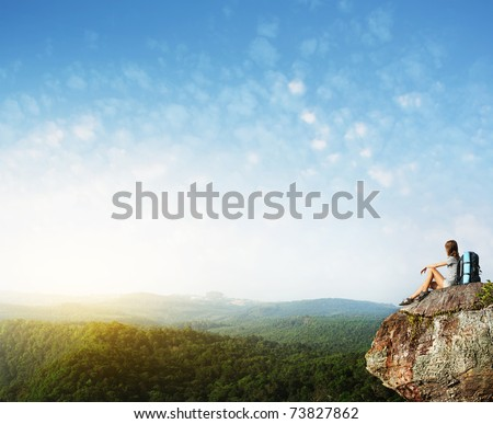 Young woman with backpack sitting on cliff's edge with raised hands and looking to a sky - stock photo
