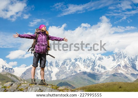 Young woman with backpack standing and looking to a sky with raised hands
