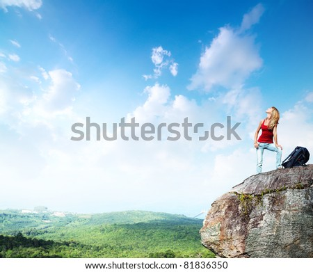 Young woman with backpack standing on a cliff's edge and looking to a sky - stock photo