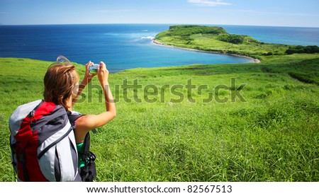 Young woman with backpack standing on a hill with green grass and making snapshot of a beautiful scene - stock photo