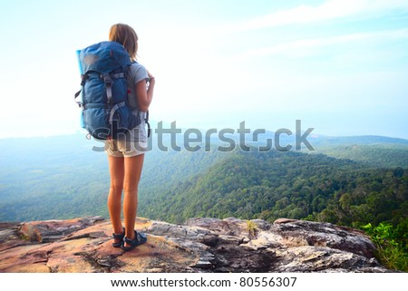 Young woman with backpack standing on a rock and looking to a valley below