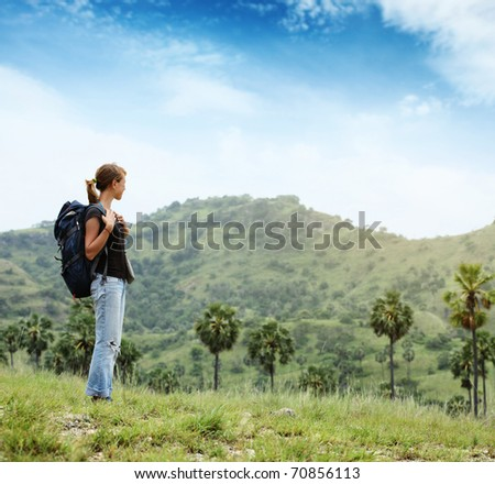 Young woman with backpack standing on cliff's edge and looking to somewhere