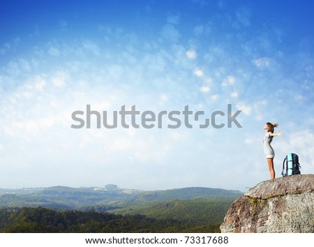Young woman with backpack standing on cliff's edge with raised hands and looking to a sky - stock photo