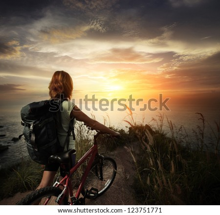 Young woman with backpack standing on ground near her bicycle and enjoying sunset over sea - stock photo