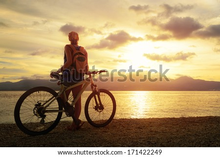 Young woman with backpack standing on the shore near his bike and enjoying the sunset over the sea on the background of the island - stock photo