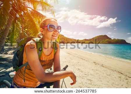 Young woman with backpack standing on the shore near his bike and looking on sea. Traveling along Asia, active lifestyle concept - stock photo
